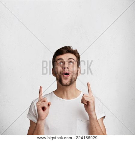 European Male Model Covers Hands, Looks In Terror, Dressed In Casual T Shirt, Isolated Over White St