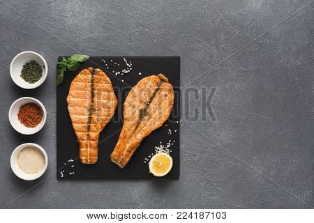 Salmon juicy fillet grilled on barbecue, served with spices assortment. Healthy seafood, red fish steak top view, restaurant food, mediterranean cuisine concept