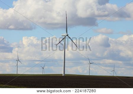 Protection of nature. Wind turbines eco power generator for renewable energy production. Alternative green clean energy, ecology. Cloudy sky meadow.