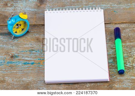 Notebook and alarm clock on wooden background. With copy space.