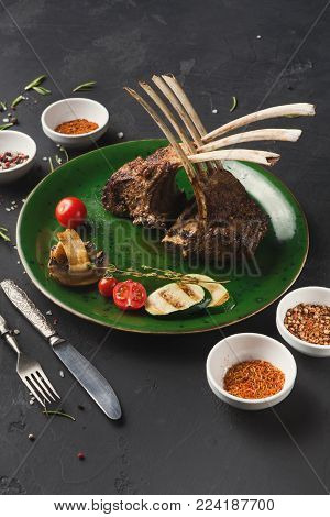 Rack of Lamb with grilled vegetables with cutlery. Restaurant serving of bbq meat with mushroom, zucchini and cherry tomato, closeup