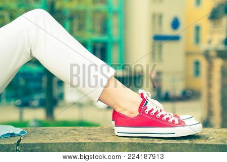 Girl in sneakers lying on the bench