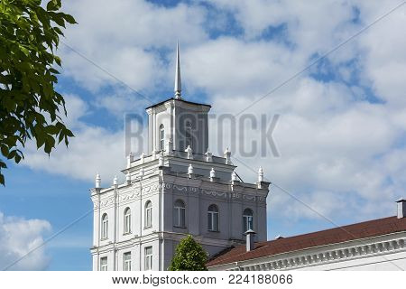High square building with a spire on the roof against the blue sky and clouds