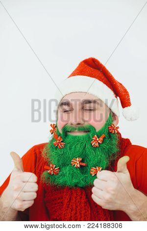 Santa Clause in red clothes with green beard decorated with red bows shows thumb-up sign