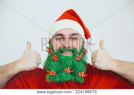 Santa Clause in red clothes with green beard decorated with red bows shows thumb-up signs and smile