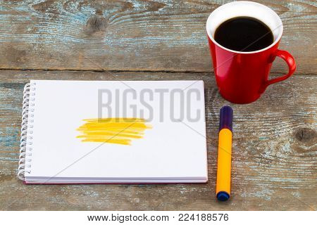 Open notebook with handwritten drawn yellow highlighter stripes and cup of coffee on wooden desk.