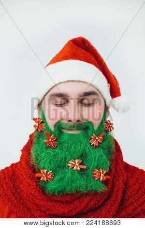 Santa Clause in red clothes with green beard decorated with red bows like a christmas tree