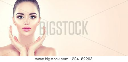 Beauty Woman Portrait. Front view spa model girl headshot. Pretty young woman touching her face. Skin care.  Youth. Beautiful Fashion Model Girl Face. Perfect Skin. On beige Background