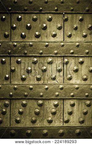 Vintage grunge wooden background door gate of the old castle detail with metal rivets