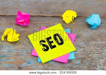SEO -  on sticky note with crumpled papers on wooden background,SEO concept.