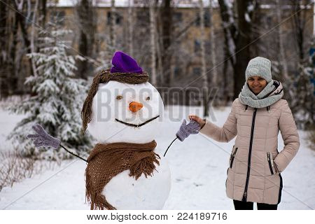 Stylish woman holds a hand of real big snowman. Beautiful woman has fun in winter park, wintertime