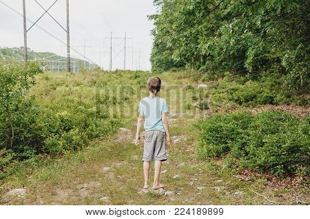 barefoot boy standing on a forest path. lonely child outdoors. back view