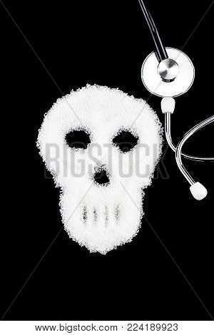 Deadly sugar addiction suggested by spilled white sugar crystals forming a skull. Diabetes mellitus concept.