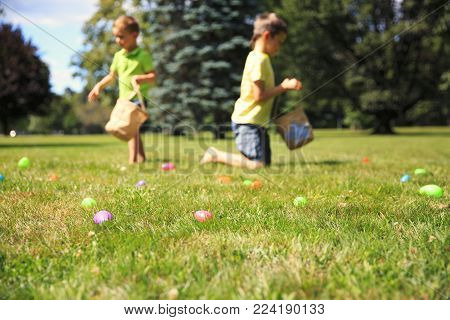 Easter eggs hunting outdoors. children looking for Easter eggs in the grass. blurred background