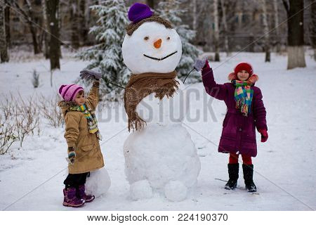 A small cheerful girls near big funny snowman. A cute little sisters has fun in winter park, wintertime
