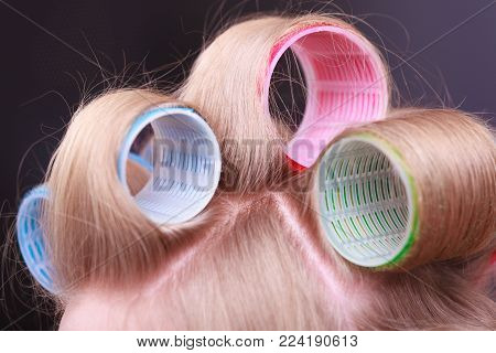 Part of woman head. Blond girl with hair curlers rollers by hairdresser in hairdressing beauty salon. Hairstyle.
