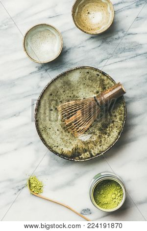 Flat-lay of Japanese tools and ceramic bowls for brewing matcha tea. Matcha powder in tin can, Chashaku spoon, Chasen bamboo whisk, Chawan bowl, cups for ceremony, grey marble background, top view