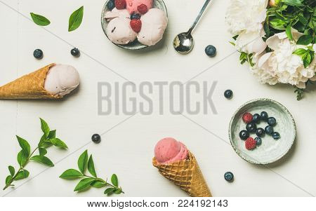 Flat-lay of Pink strawberry and coconut ice cream scoops, sweet cones, peony flowers bouquet and fresh berries in bowl over white background, top view, copy space. Summer food concept