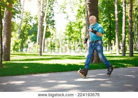 Active old age. Happy senior man doing tricks on roller skates outdoors. Elderly man enjoying sports in sunny summer park . Healthy lifestyle concept, copy space