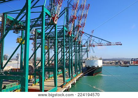 Huge container handling gantry cranes at a container terminal. Car cargo ship and Blue sky background