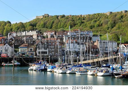 Scarborough, North Yorkshire, England - 6th May 2016: Scarborough harbor and marina with castle in background. This is a popular tourist resort.