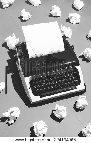 Oldschool typewriter and pieces of creased paper nearby. Black and white.