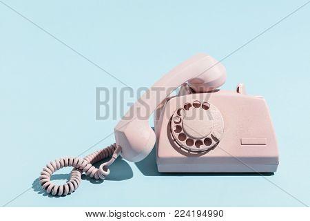 Oldschool pink telephone on a blue background. Telecommunication. Vintage objects.