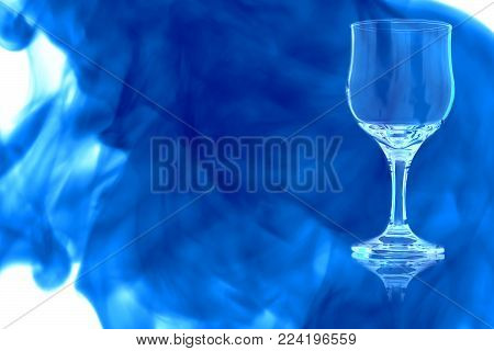 An empty white wine glass on white background enveloped in puff of blue smoke.
