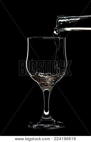Glass of a white wine is pouring wine from a bottle of white. Filmed in close-up glass, where you pour the wine from the bottle.