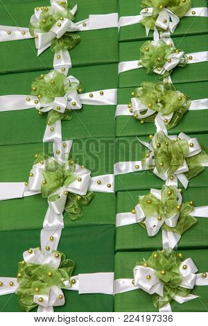 Lot of green gift boxes with white ribbon and bow