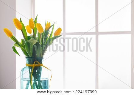 Beautiful flowers bouquet background. Yellow tulips in window backlight with copy space. Mockup for greeting card