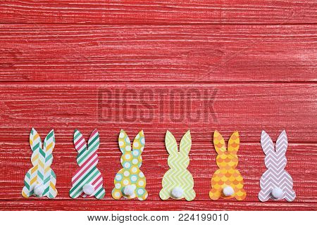 Easter bunnies made from patterned paper on wooden background