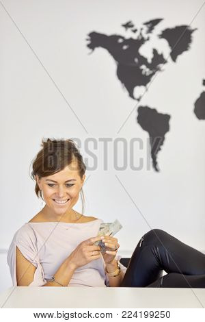 Young smiling woman sits with several banknotes in hands at desk.