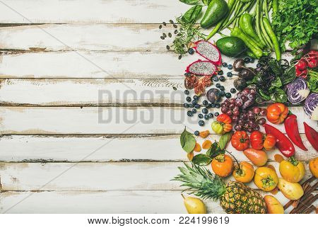 Helathy raw vegan food cooking background. Flat-lay of fresh fruit, vegetables, greens, superfoods over white wooden table, top view, copy space. Clean eating, alkaline diet, vegetarian concept