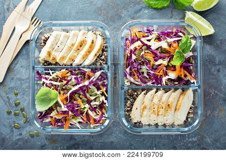 Healthy meal prep containers with quinoa, chicken and cole slaw overhead shot