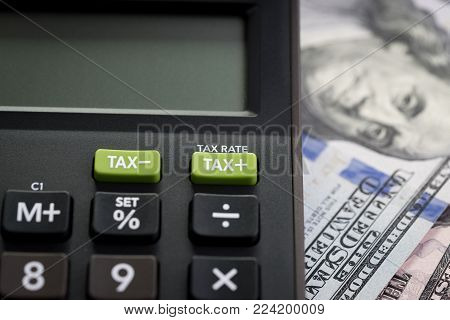 Tax cuts or reduce concept, Closed up shot of TAX minus / plus buttons with text TAX RATE on calculator with background of blurred US Dollar banknotes, United States government tax overhaul policy.
