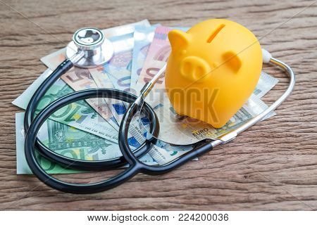 EU European union economic or finance health check concept, saving piggy bank with stethoscope on pile of Euro banknotes on wooden table, debt and financial crisis on Europe countries.