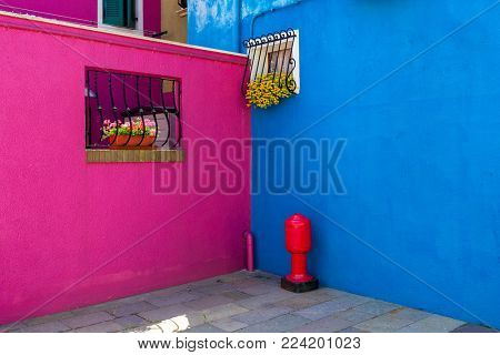Purplish red and vivid blue colored walls of small houses on island of Burano in Venice, Italy.