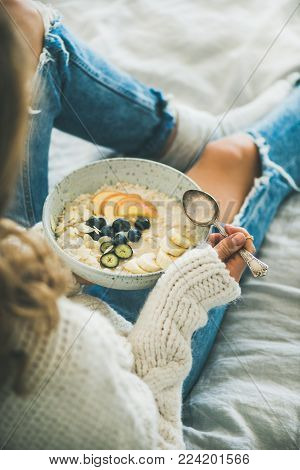 Healthy winter breakfast in bed. Woman in woolen sweater and shabby jeans eating vegan almond milk oatmeal porridge with berries, fruit and almonds. Clean eating, vegetarian food concept