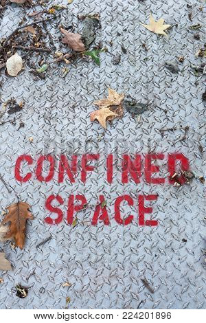 A sign warns of confined space in bright red