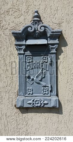 An old mail box fixed to a wall. The word Correio means Mail in portuguese.