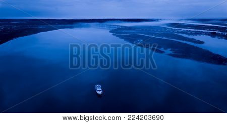 aerial view of boat and fog on water in early dawn hours.