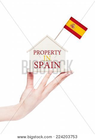 Female hand holding wooden house model with Spain flag on top. Property in Spain text