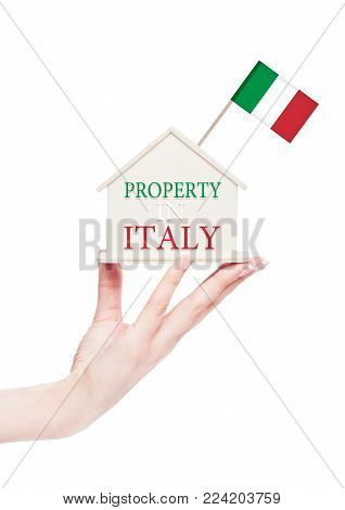 Female hand holding wooden house model with Italy flag on top. Property in Italy text