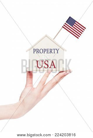 Female hand holding wooden house model with United States of America flag on top. Property in USA text