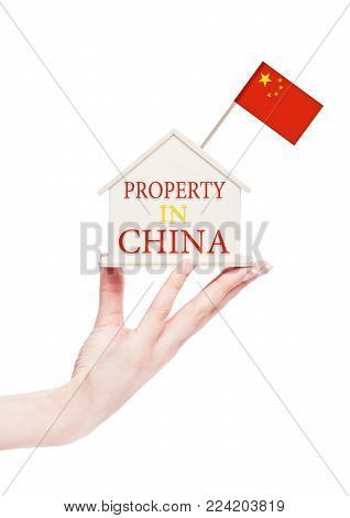 Female hand holding wooden house model with China flag on top. Property in China text