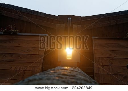 Light lamp under the wooden roof, with dark wooden beams