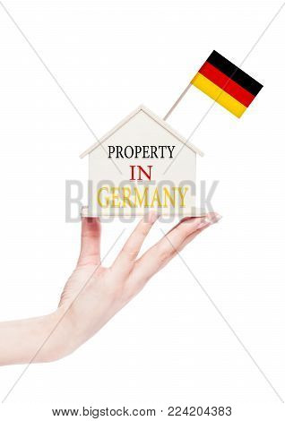 Female hand holding wooden house model with Germany flag on top. Property in Germany text