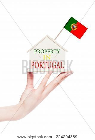 Female hand holding wooden house model with Portugal flag on top. Property in Portugal text