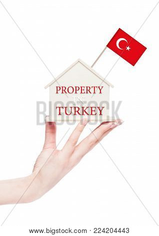 Female hand holding wooden house model with Turkey flag on top.Property in Turkey.